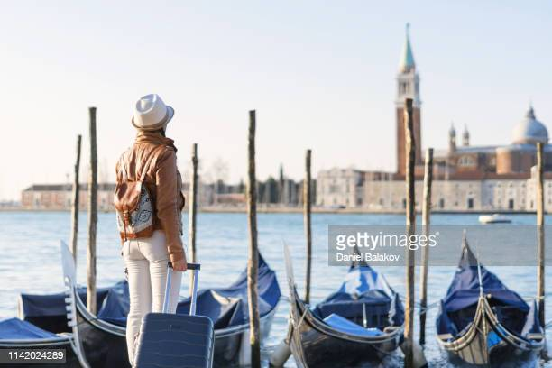ws. rear view of a young woman solo traveler with a black suitcase in front of the gondolas at san marco square in venice, italy, at sunrise. daydreaming. - gondola traditional boat stock pictures, royalty-free photos & images