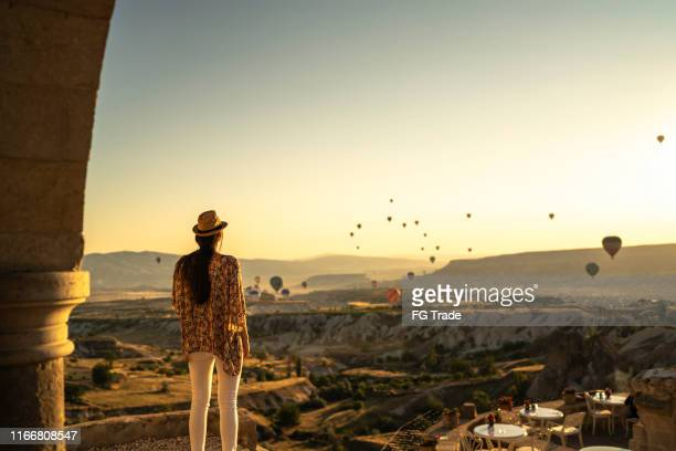 rear view of a young woman standing and looking at view during ballooning festival - unesco world heritage site stock pictures, royalty-free photos & images