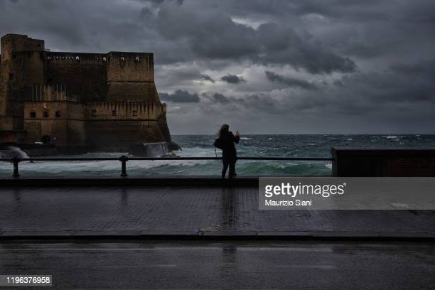 rear view of a young woman standing on seafront promenade , against cloudy sky - one young woman only stock pictures, royalty-free photos & images