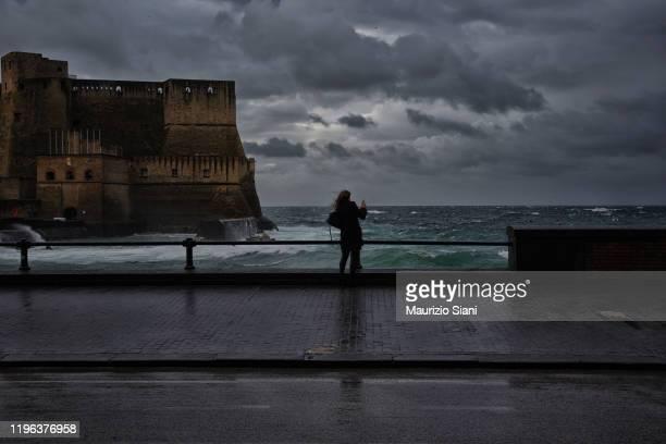 rear view of a young woman standing on seafront promenade , against cloudy sky - endast en ung kvinna bildbanksfoton och bilder
