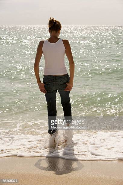 rear view of a young woman standing on the beach - rolled up trousers stock pictures, royalty-free photos & images