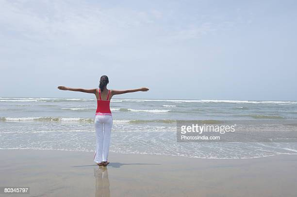 Rear view of a young woman standing on the beach with her arms outstretched