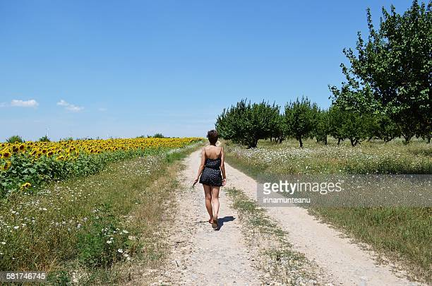 Rear view of a young woman walking down path