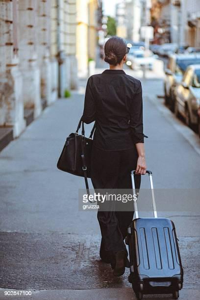 Rückansicht einer jungen Frau die Straße entlang und ziehen einen kleinen Koffer