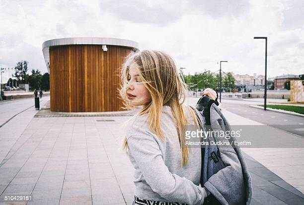 rear view of a young woman with windy blonde hair outdoors - casacca foto e immagini stock