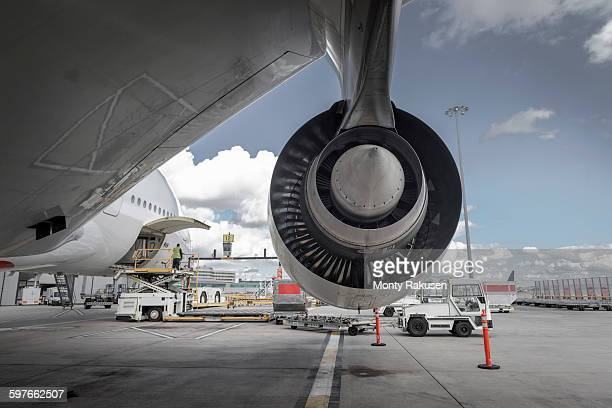 Rear view of A380 jet engine with ground crew loading freight