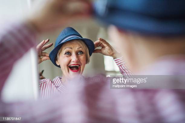 a rear view of active senior woman trying on a new hat, looking in the mirror. - anprobieren stock-fotos und bilder