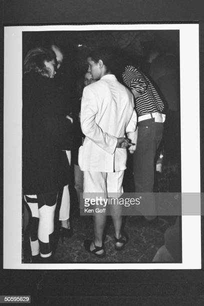Rear view of actor Jaye Davidson clad in white bermuda shorts suit flipping the bird w middle finger of his left hand which he is holding behind his...