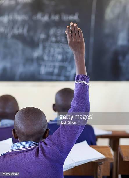 rear view of african schoolboy (10-12) in classroom raising his hand up - hugh sitton stock-fotos und bilder