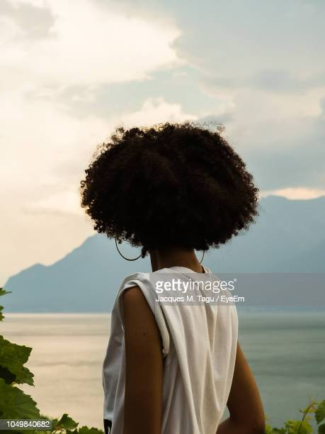 rear view of afro woman looking at lake during sunset - afro frisur stock-fotos und bilder