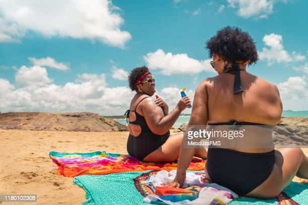 rear view of afro women using suntan lotion at beach - chubby stock pictures, royalty-free photos & images