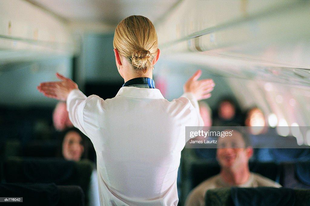 Rear View of Air Stewardess Explaining Aeroplane Safety to Passengers : Stock Photo