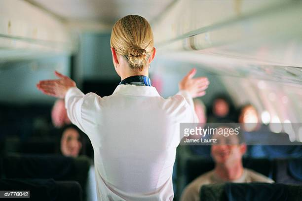 rear view of air stewardess explaining aeroplane safety to passengers - commercial aircraft stock photos and pictures