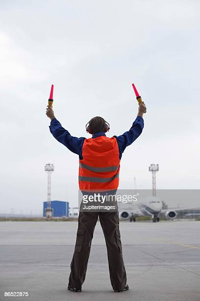 Rear view of airport hangar worker directing plane on tarmac