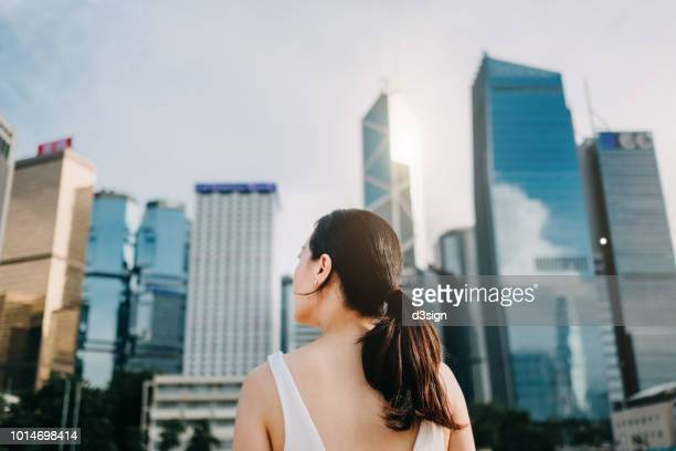 rear view of ambitious businesswoman looking towards the urban financial towers in central business district - cadrage aux genoux photos et images de collection