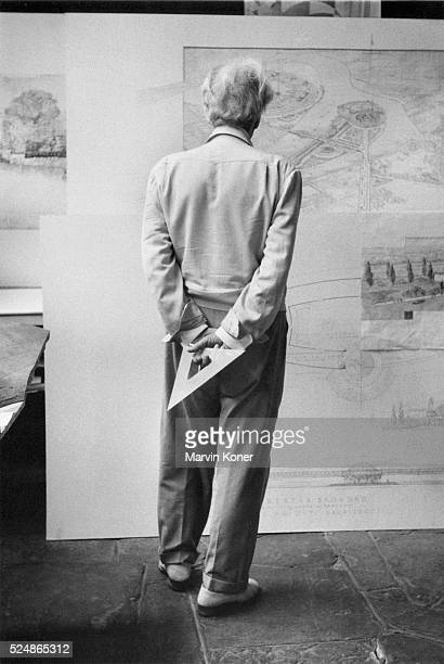 American architect Frank Lloyd Wright holds a drafting triangle and turns his back to look at architectural drawings on the wall in Oak Park Illinois