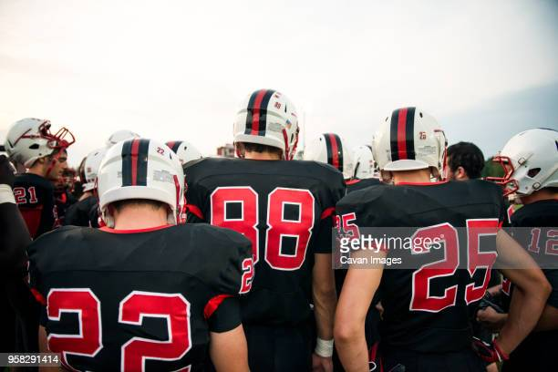 rear view of american football players against sky - high school football stock pictures, royalty-free photos & images