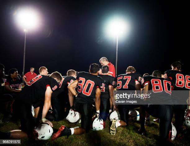 rear view of american football players kneeling on illuminated field at night - high school football stock pictures, royalty-free photos & images