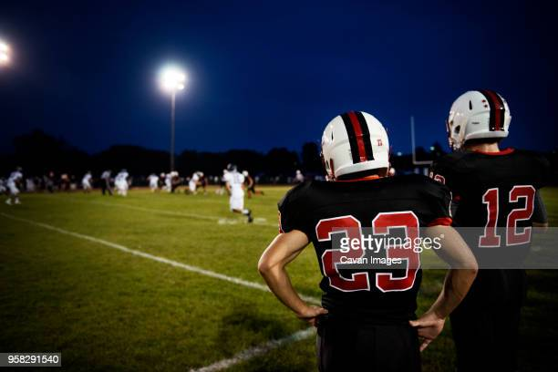 rear view of american football players standing on football field - high school football stock pictures, royalty-free photos & images