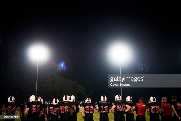 rear view of american football players standing on illuminated field against sky - amerikanischer football stock-fotos und bilder