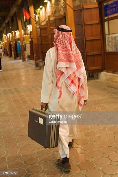 Rear View of an Arab Man Walking with Suitcase. Dubai, United Arab Emirates