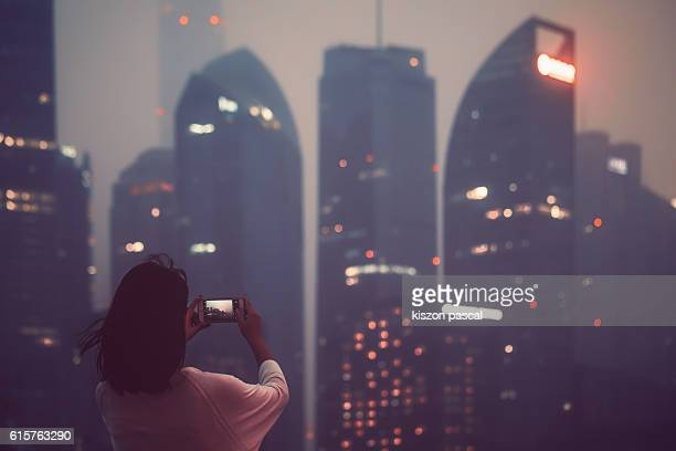 Rear view of an asia young woman with winds bowing the hairs photographing the urban skyline in night ( Shanghai , China )