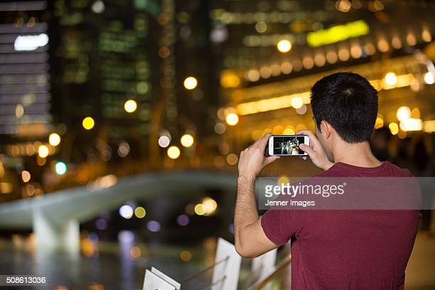 Rear view of an Asian man taking photo at night of city.