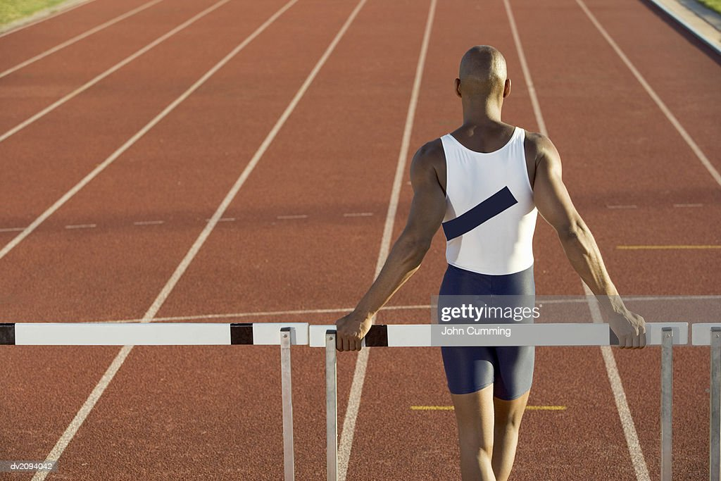 Rear View of an Athlete Standing in Front of a Hurdle on a Track : Stock Photo