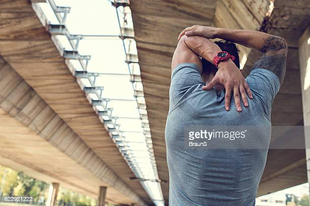 Rear view of an athlete stretching his arm outdoors.