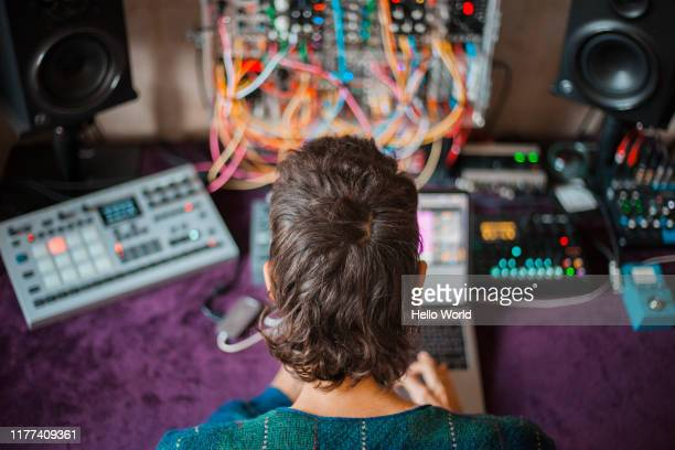 rear view of an electronic music producer in studio mixing sounds - musician stock-fotos und bilder