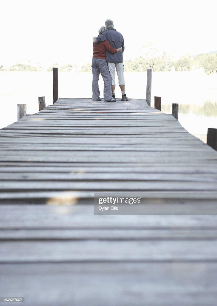 Rear View of an Embracing Couple Standing on a Pier : Stock Photo
