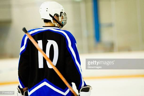 Rear view of an ice hockey player holding an ice hockey stick