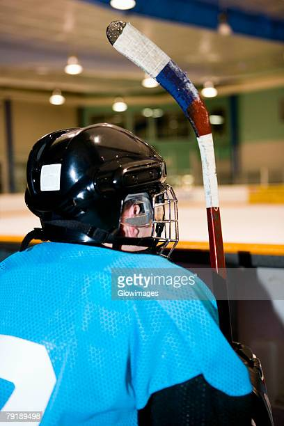 rear view of an ice hockey player sitting next to the railing of an ice rink - ice hockey uniform stock pictures, royalty-free photos & images