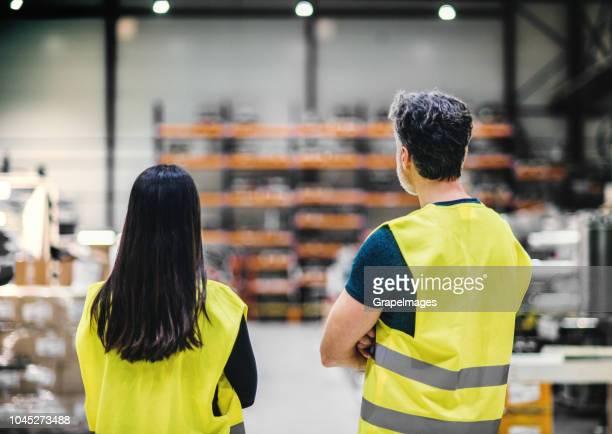 een achteraanzicht van een industriële man en vrouw ingenieurs in een fabriek, gekruiste armen. - vest stockfoto's en -beelden