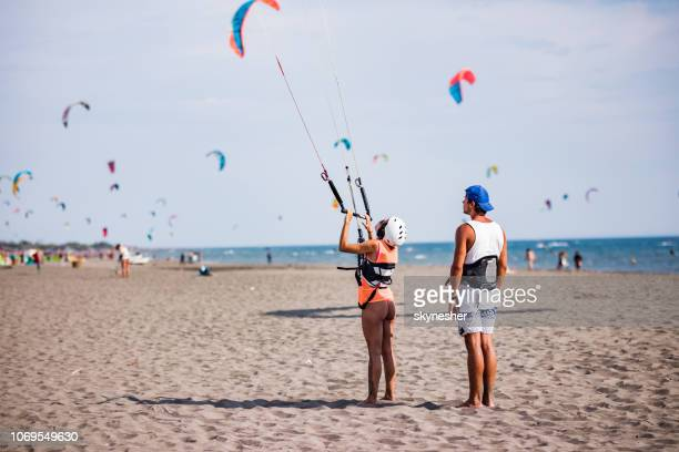 rear view of an instructor preparing a woman for kitesurfing on the beach. - kite toy stock photos and pictures