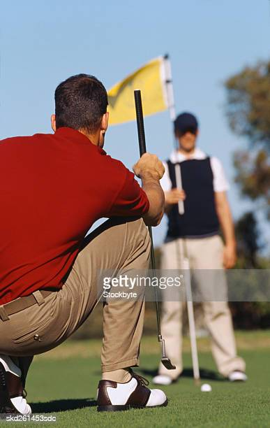 Rear view of an mid-adult man watching a golf ball roll on the course