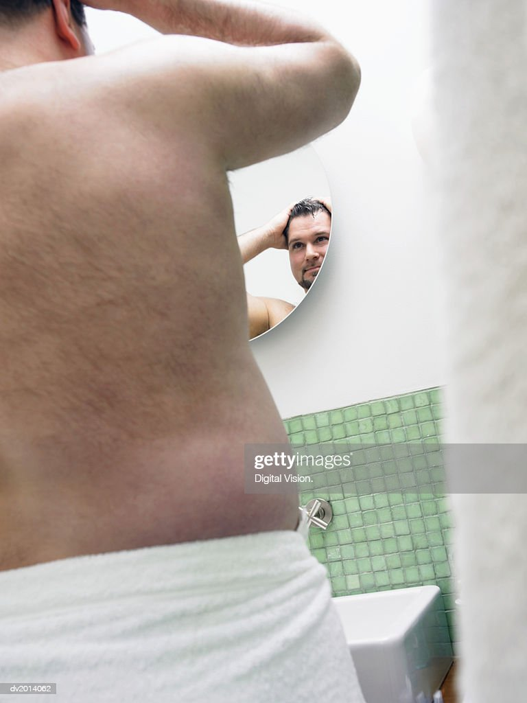 Rear View of an Overweight Man Wrapped in a Towel, Looking at a Bathroom Mirror : Stock Photo