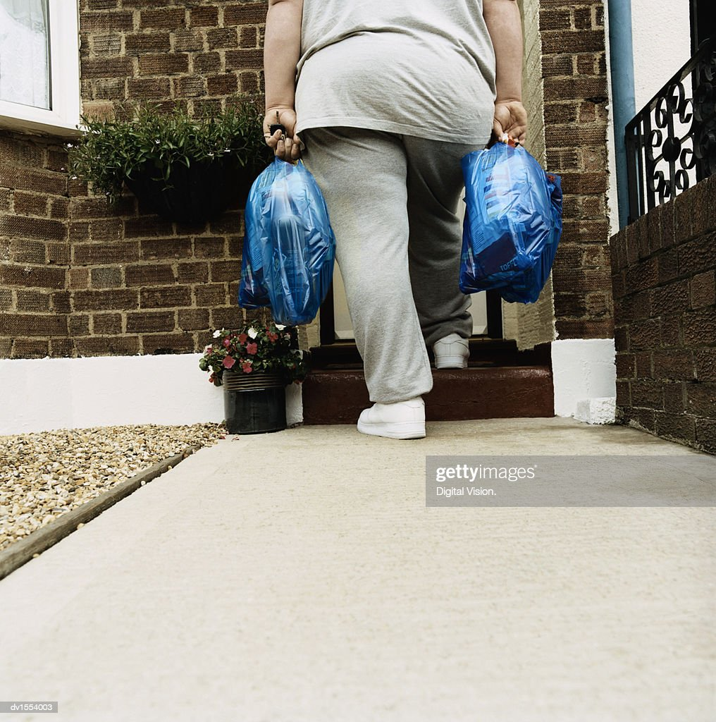 Rear View of an Overweight Person Standing With Shopping Bags on a Doorstep : Stock Photo