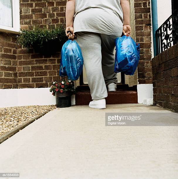 Rear View of an Overweight Person Standing With Shopping Bags on a Doorstep
