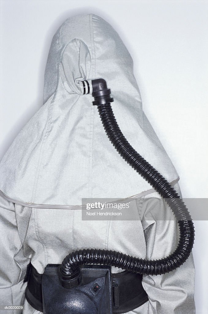 Rear View of an Unrecognizable Person Wearing a Protective Suit with a Tube Attached to a Hood : Stock Photo
