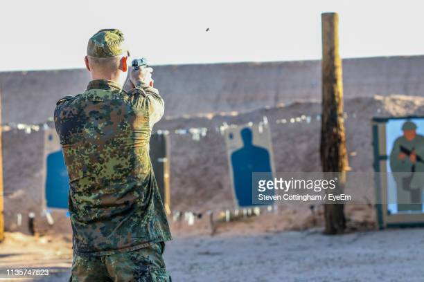 rear view of army man shooting with handgun against wall - steven cottingham stock-fotos und bilder