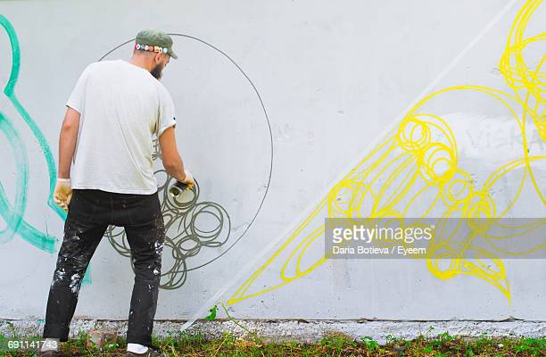 Rear View Of Artist Spraying On Wall