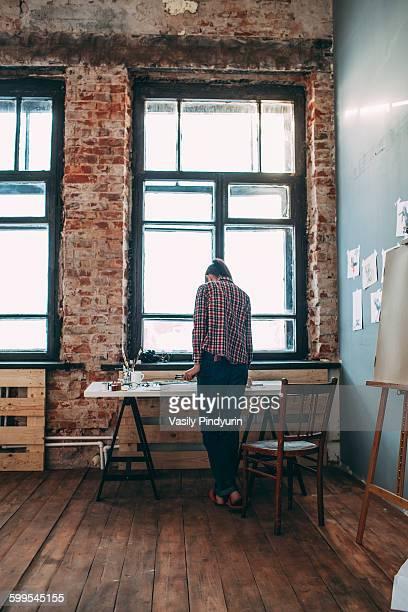 Rear view of artist standing in art studio