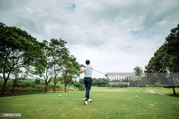 アジアの中国の若い男性ゴルファーの背面図は、ゴルフコースで彼のドライバークラブをティーオフし、スイング - ゴルフのスウィング ストックフォトと画像
