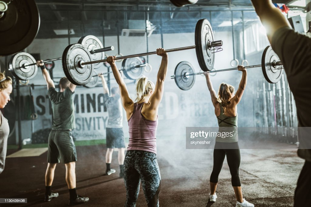 Rear view of athletic people exercising with barbells on sports training in a gym. : Stock Photo