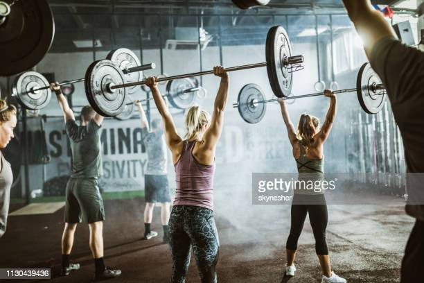 rear view of athletic people exercising with barbells on sports training in a gym. - snatch weightlifting stock photos and pictures