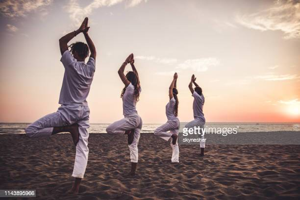 rear view of athletic people in tree pose on the beach at sunset. - tree position stock photos and pictures