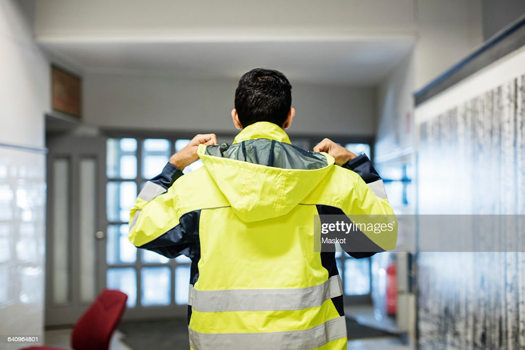 Rear view of auto mechanic student wearing reflective jacket in workshop : Stock Photo