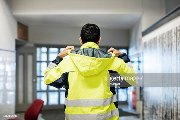 rear view of auto mechanic student wearing reflective jacket in workshop - jaqueta - fotografias e filmes do acervo