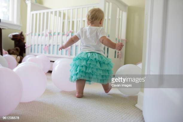 rear view of baby girl playing with balloons at her first birthday party - first birthday stock pictures, royalty-free photos & images